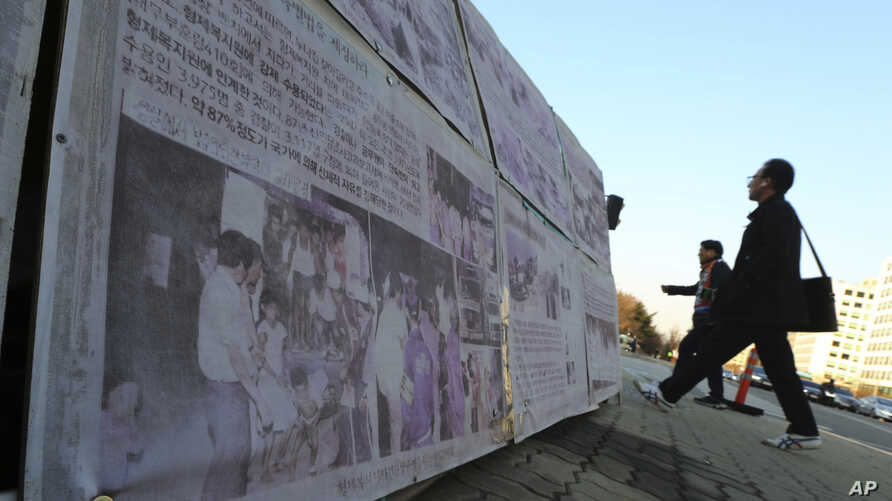 FILE - People walk past a photo of guards unloading children from a truck at the Brothers Home in Busan, at a display in front of National Assembly in Seoul, South Korea, April 2, 2019.