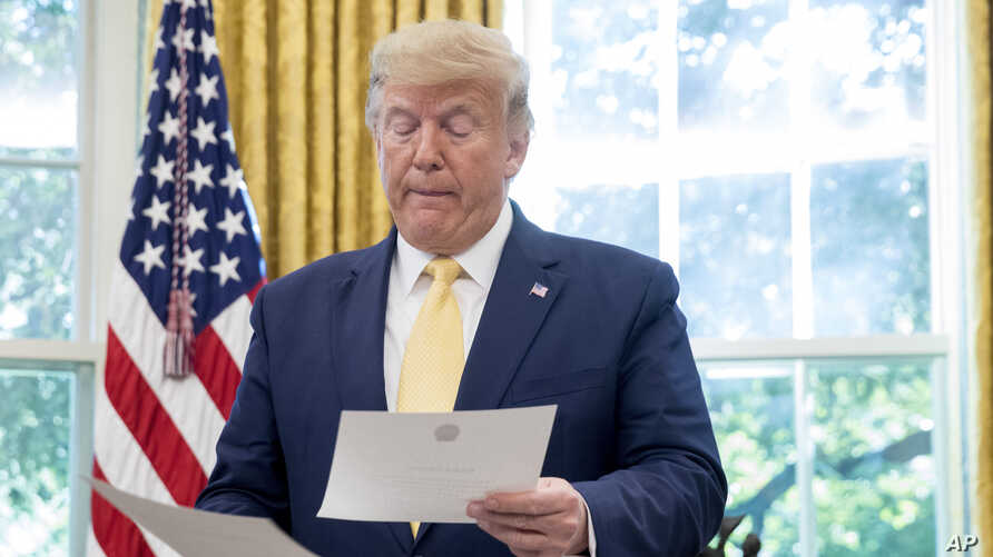 FILE - President Donald Trump is seen holding documents in the Oval Office of the White House, in Washington, Oct. 11, 2019.