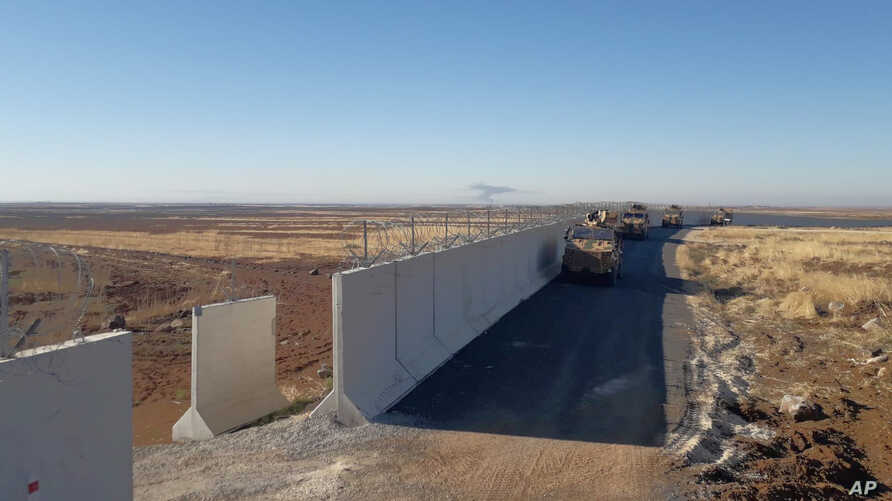 Turkish army armored vehicles arrive at a meeting point near the Turkish town of Idil at the Turkey-Syria border before Turkish and Russian troops conduct their third joint patrols in northeast Syria, Nov. 8, 2019.