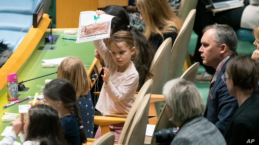 A young member of the Polish delegation shows off a drawing she made during the 30th anniversary of the adoption of the Convention on the Rights of the Child at United Nations headquarters in New York.