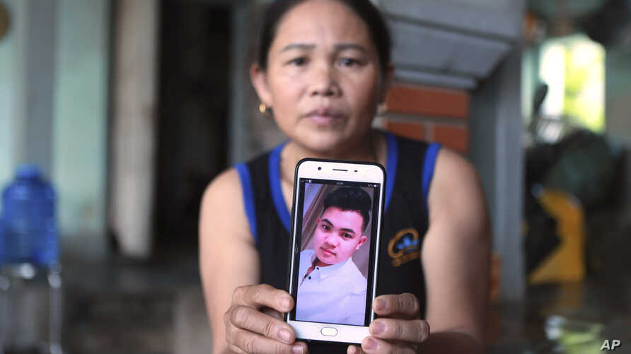Hoang Thi Ai holds up her phone showing a photo of her son, Hoang Van Tiep, who she fears is one of the possible victims in the truck deaths in England, at her home in Dien Chau district, Nghe An province, Vietnam, Oct. 28, 2019.