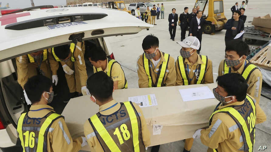 Airport personnel load a coffin into an ambulance at the Noi Bai airport, Nov. 27, 2019 in Hanoi, Vietnam. The bodies of 16 of the 39 Vietnamese who died in a truck in Britain last month have been repatriated to their homeland.