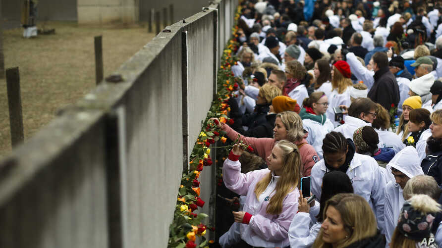 People stick flowers in the remains of the Berlin Wall during a commemoration ceremony to mark the 30th anniversary of the wall's fall at a memorial site at Bernauer Strasse in Berlin, Germany, Nov. 9, 2019.