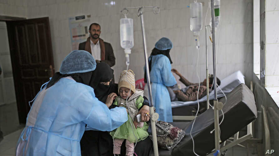 FILE - A girl, center, suspected of being infected with cholera, is treated at a hospital in Sanaa, Yemen, Sept. 9, 2019.