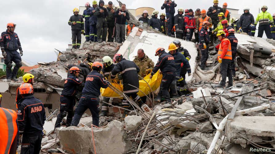 Emergency personnel carry a body during a search for survivors in a collapsed building in Durres, after an earthquake shook Albania, Nov. 28, 2019.