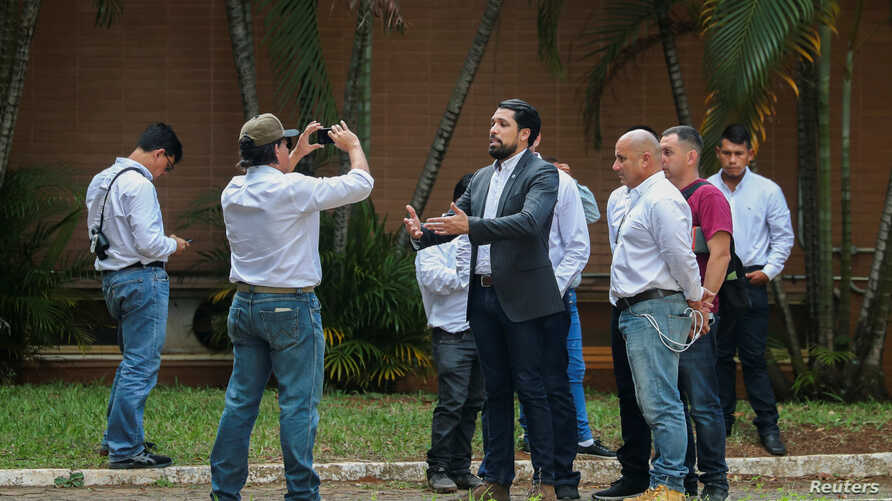 Supporters of Venezuela's opposition leader Juan Guaido record a video from the grounds of the Venezuelan embassy in Brasilia, Brazil, Nov. 13, 2019.