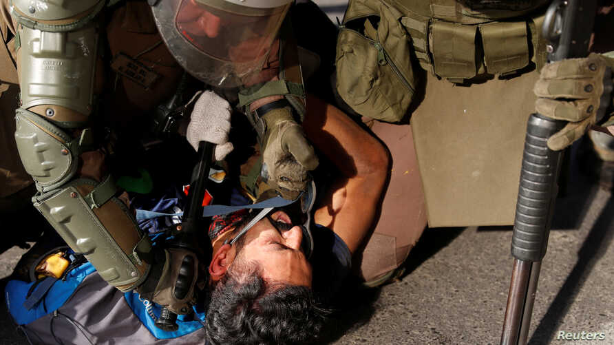 A policeman hits a detained demonstrator in the face during a protest against Chile's government in Santiago, Nov. 20, 2019.