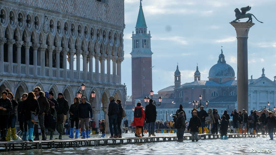 People walk through across a makeshift walkway over the flooded St. Mark's Square in Venice, Italy.