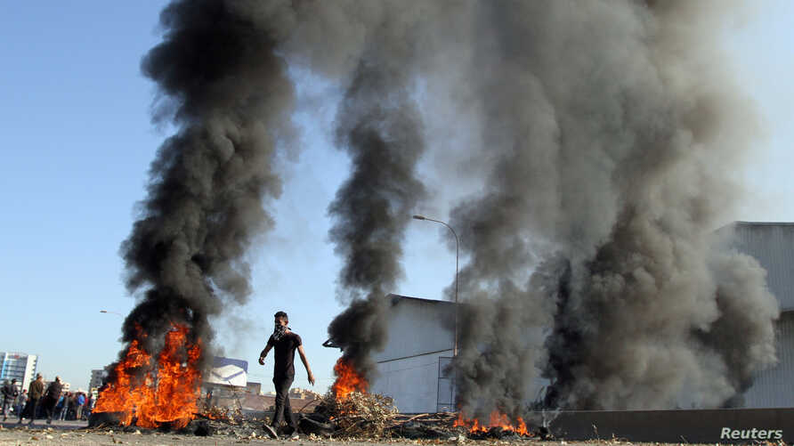 A demonstrator walks near burning tires during ongoing anti-government protests in Tripoli, Lebanon, Nov. 12, 2019.