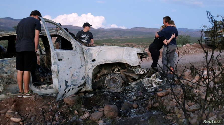 Relatives of slain members of Mexican-American families belonging to Mormon communities observe the burnt wreckage of a vehicle where some of their relatives were killed, in Bavispe, Sonora state, Mexico, Nov. 5, 2019.