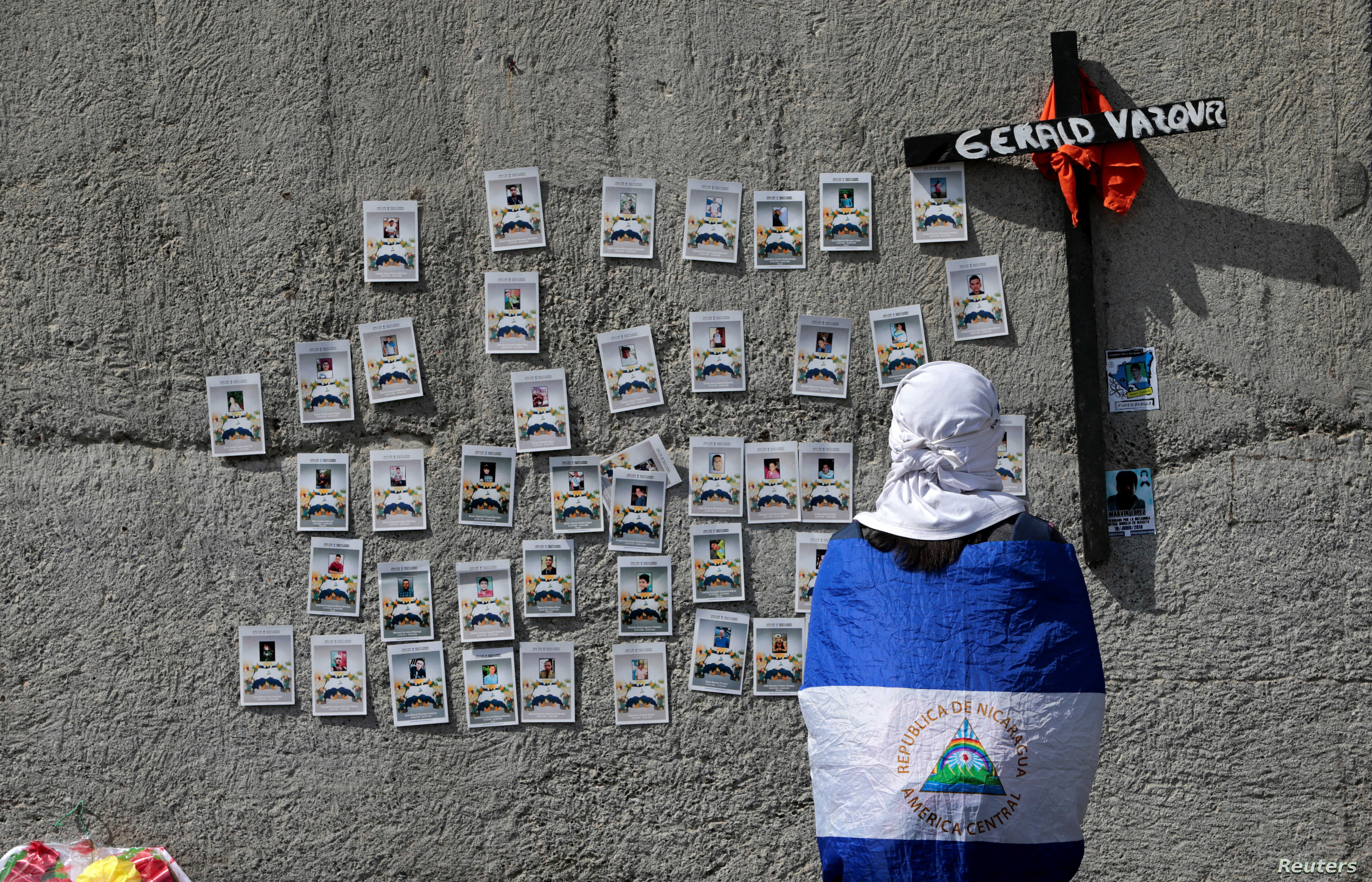 A demonstrator wearing the national flag looks at pictures of protesters who died during the protests against Nicaraguan President Daniel Ortega's government last year, in Managua, Nov. 2, 2019.