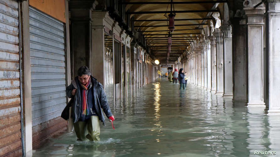 A person walks in the flooded St. Mark's Square during a period of seasonal high water in Venice, Italy, Nov. 12, 2019.