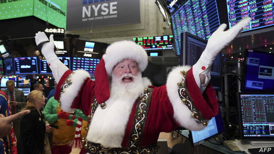 Santa Clause gestures on the floor at the closing bell of the Dow Industrial Average at the New York Stock Exchange on December…