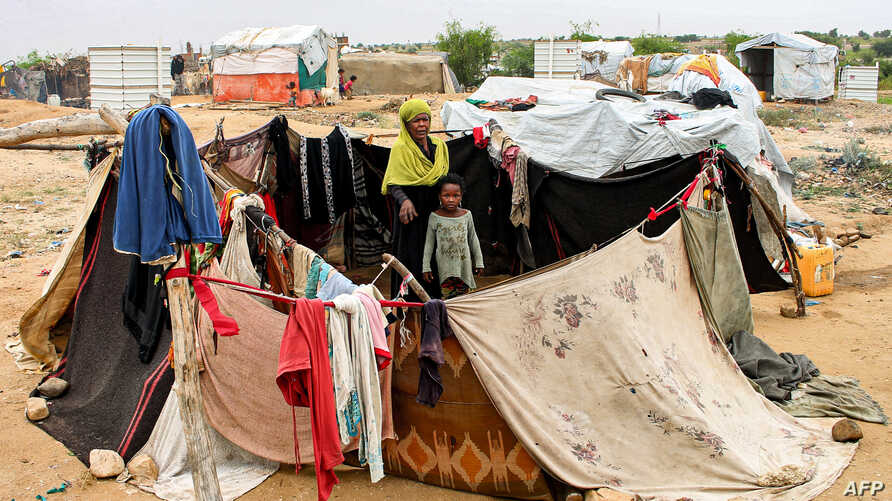 A woman and child sit together in an enclosure made from fabrics at a make-shift camp for displaced Yemenis in the northern…