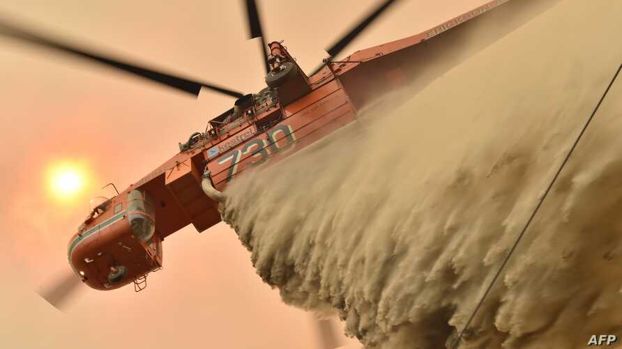A helicopter drops fire retardent to protect a property in Balmoral, Australia