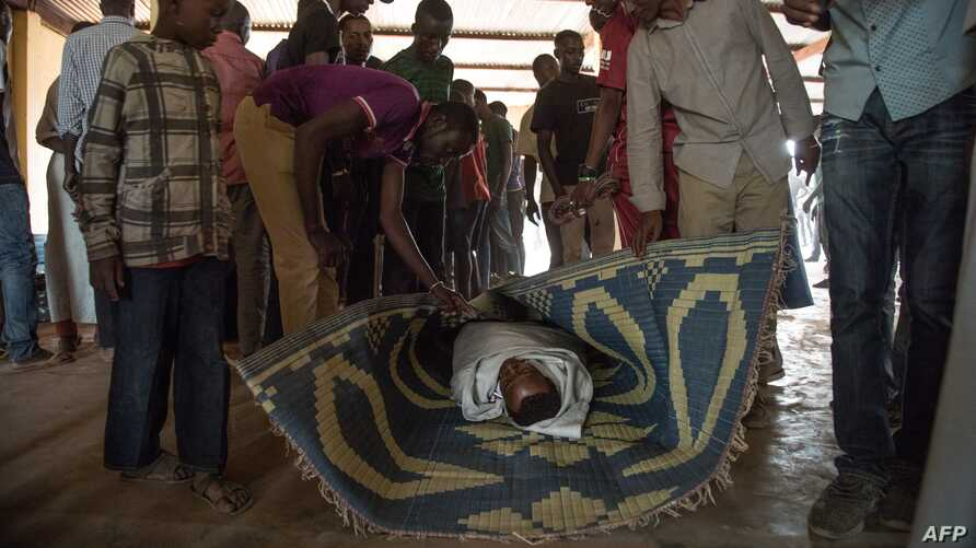 People look at the body of a man lying in the Ali Babolo Mosque, in the PK5 district in Bangui on December 26, 2019, after…