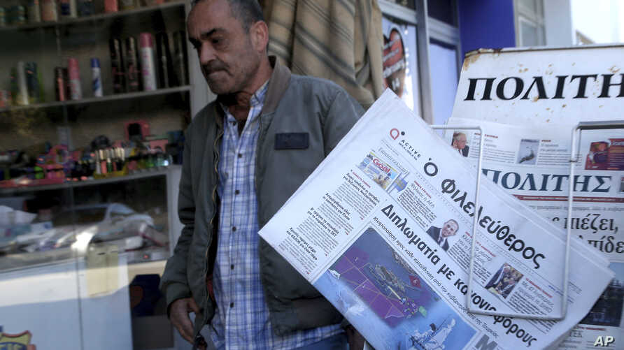 A man reads walks past  Cypriot newspaper with a  front page carrying  a photo montage about Turkey's actions over Cyprus and…