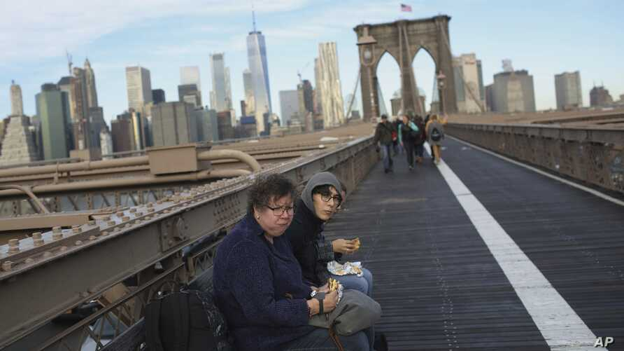 FILE - People eat their breakfast on the Brooklyn Bridge where the Manhattan skyline is seen in the background at the start of a work day, Dec. 3, 2018, in New York.