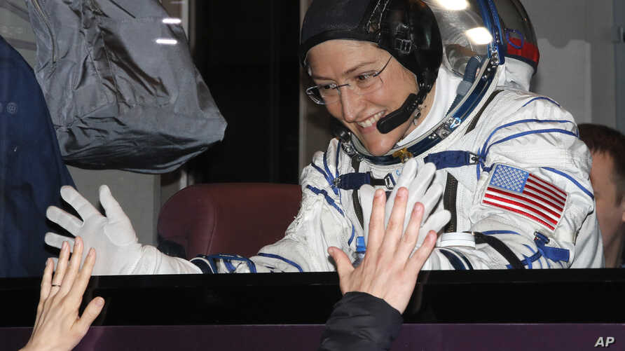 U.S. astronaut Christina Hammock Koch, member of the main crew of the expedition to the International Space Station, gestures to her relatives from a bus prior the launch of Soyuz MS-12 space ship, Baikonur cosmodrome, Kazakhstan, March 14, 2019.