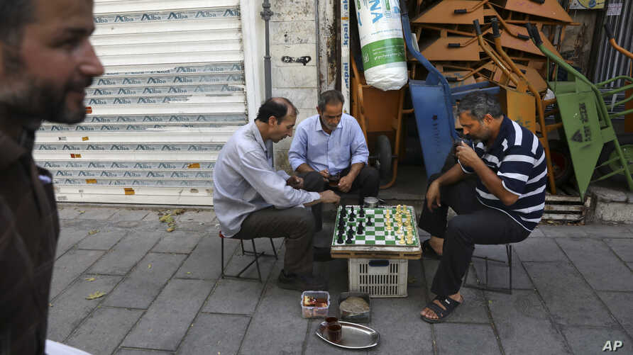 Men play chess outside their shop in downtown Tehran, Iran, July 17, 2019.
