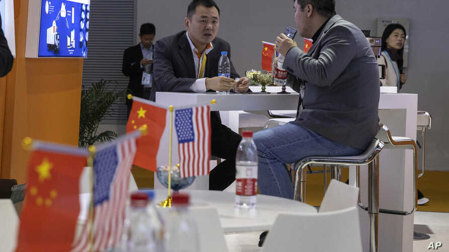FILE - In this Nov. 6, 2019, file photo, visitors chat near American and Chinese flags displayed at a booth