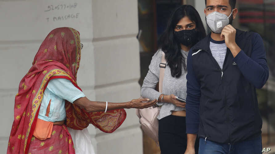 An elderly Indian woman seeks alms as youth wearing pollution masks walk through a shopping area in New Delhi, India, Nov. 14, 2019.
