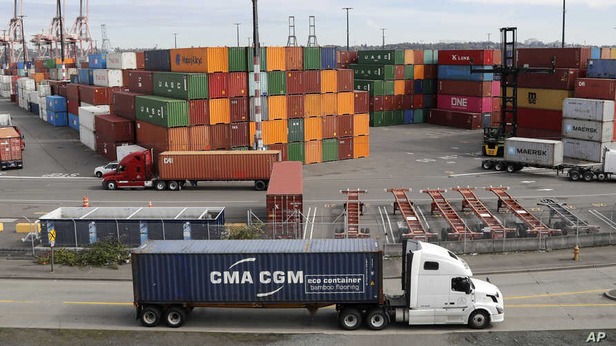 FILE - In this Oct. 2, 2019, file photo trucks hauling shipping containers drive near containers stacked five-high at a…