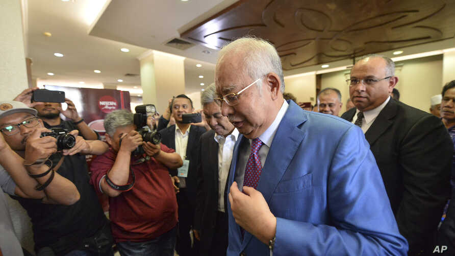 Former Malaysian Prime Minister Najib Razak, center, walks out from the courtroom at the court house in Kuala Lumpur, Malaysia, for his corruption trial, Dec. 3, 2019.