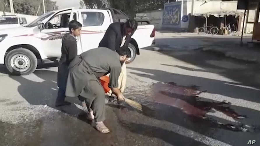 In this image made from video, locals sweep blood at the site of a gun attack on a Japanese aid worker's truck, Dec. 4.