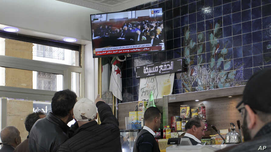 People watch the trial of former Algerian Prime Ministers Ahmed Ouyahia and Abdelmalek Sellal, in a cafe of Algiers, Wednesday,…
