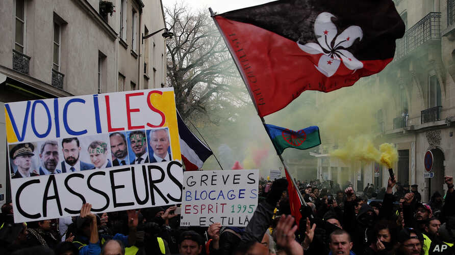"""A sign depicting French politicians and reading """"Here are the troublemakers"""" and flags with flares are displayed during the yellow vests 56th round demonstration in Paris, Dec. 7, 2019."""