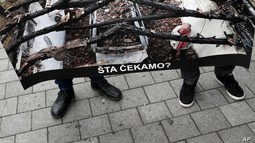 Members of the Independent Journalists' Association hold a poster shows a journalist Milan Jovanovic in his burned house that…