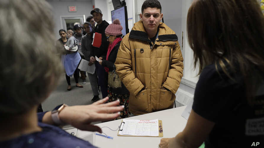 Helison Alvarenga, of Brazil, center, speaks with volunteers Marcia Previatti, front left, and Arlene Vilela, front right, at the New England Community Center, in Stoughton, Mass, Dec. 4, 2019.