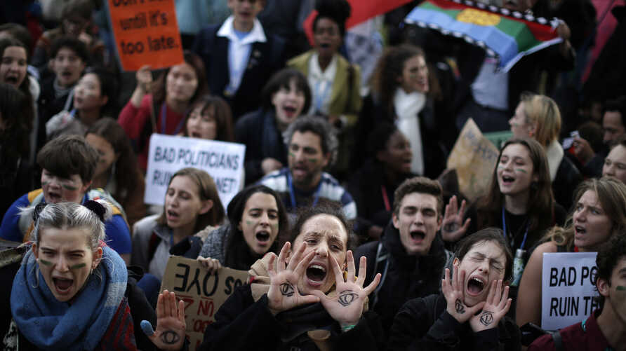 People shout slogans during a march organized by the Fridays for Future international movement of school students outside of…