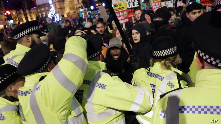 People scuffle with police during an anti-Boris Johnson demonstration, at Trafalgar Square in central London, Dec. 13, 2019.