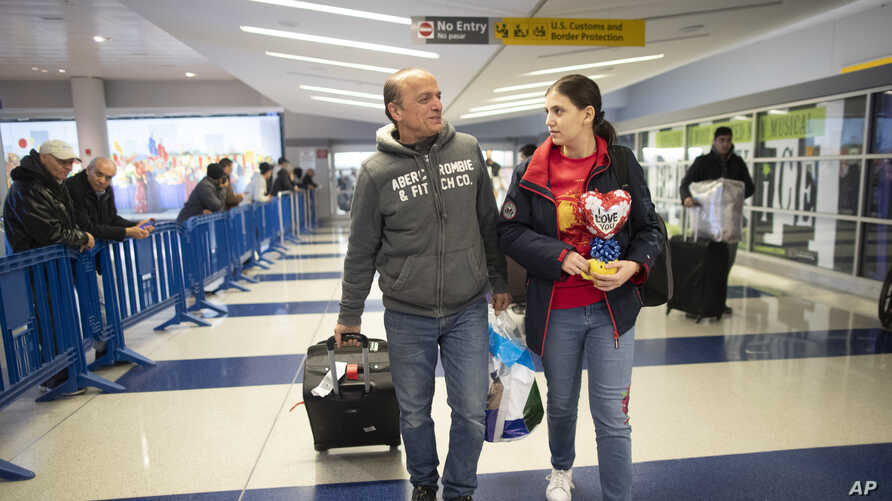 FILE - Mohammed Hafar, left, helps his daughter Jana with her luggage as they leave JFK Airport in New York, Dec. 3, 2019.