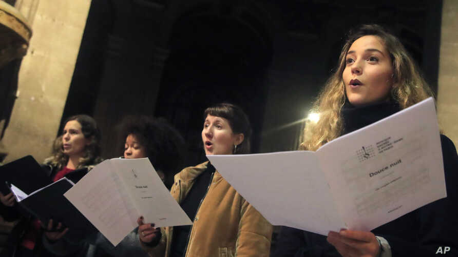 Members of the Notre Dame cathedral choir sing during a rehearsal at the Saint Sulpice church in Paris, Dec. 16, 2019.