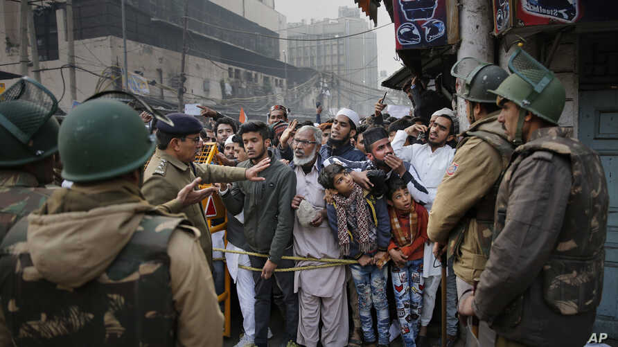 Indian policemen stop protesters at a police barricade in New Delhi, India, Dec. 20, 2019.