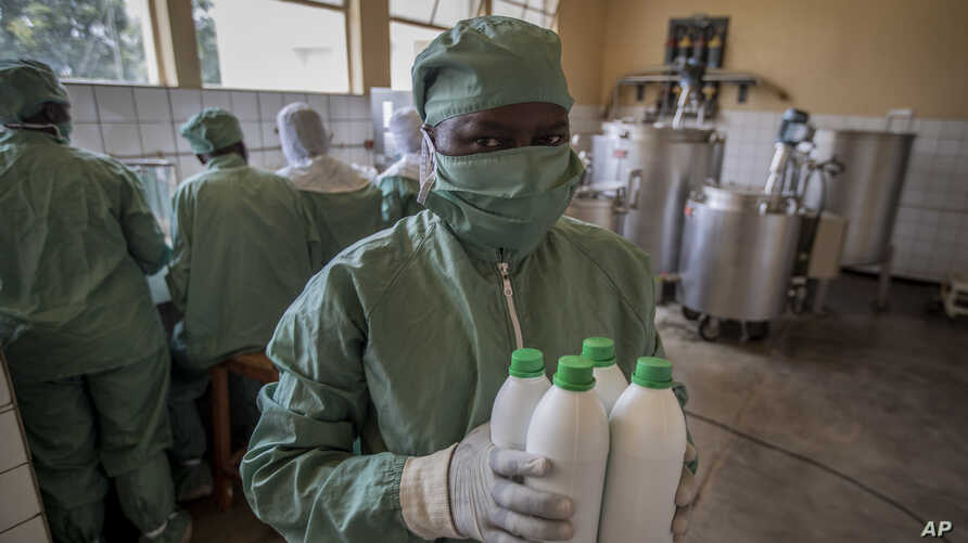 A worker carries bottles of liquid morphine after making it from powder, wearing protective clothing to protect from the effects of the drug and to prevent contamination, at the Pharmaceutical Laboratory of Rwanda in Butare, Rwanda, Nov. 7, 2019.