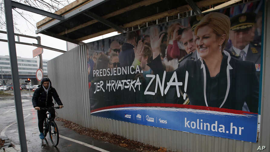 A cyclist rides past a poster of presidential candidate Kolinda Grabar Kitarovic in Zagreb, Croatia, Dec. 21, 2019.