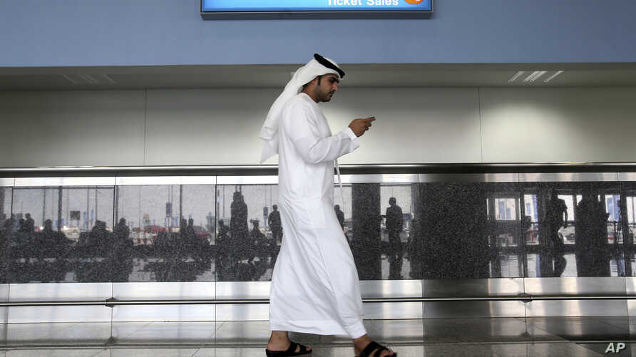 FILE - In this Oct. 27, 2013 file photo, a worker looks at his mobile phone at the newly opened Al Maktoum International…