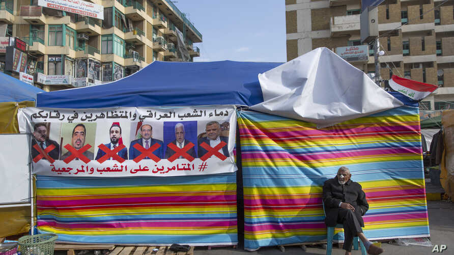 A protester sits next to a poster with defaced pictures of Iraqi politicians during ongoing protests in Tahrir square, Baghdad, Iraq, Dec. 25, 2019.