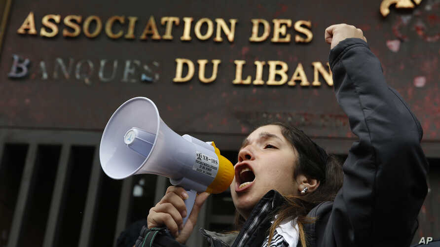 A protester leads a chant during ongoing protests against the Lebanese political class, in front of the building of the…