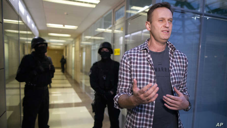 Russian opposition leader Alexei Navalny speaks to the media as policemуn stand guard at the Foundation for Fighting Corruption…