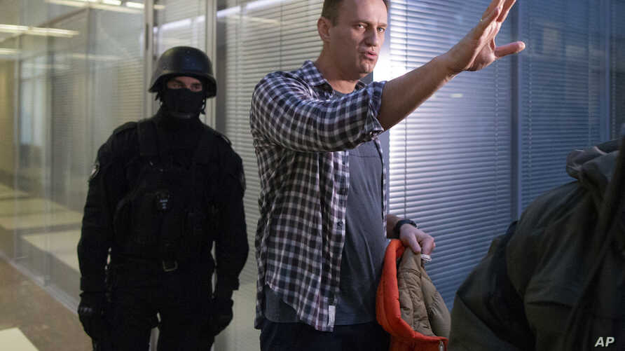 Russian opposition leader Alexei Navalny speaks to the media as a policeman stands guard at the Foundation for Fighting Corruption office in Moscow, Russia, Dec. 26, 2019.