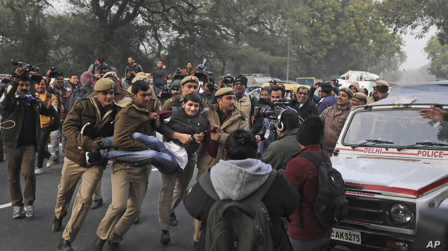 A protesting student is detained by a policemen outside Uttar Pradesh Bhawan during a protest against a new citizenship law and violence by police in the state, in New Delhi, India, Dec. 27, 2019.