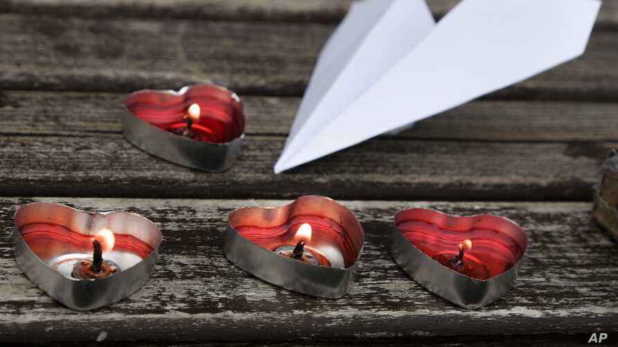 Candles in the shape of hearts and a paper aeroplane are placed near the Almaty International Airport, outside Almaty, Kazakhstan, Dec. 28, 2019.