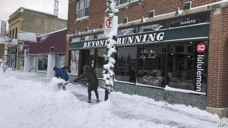 Jake Olson, left, and Mackenzie Weinberger shovel snow outside of a store in downtown Fargo, N.D. on Monday, Dec. 30, 2019,…