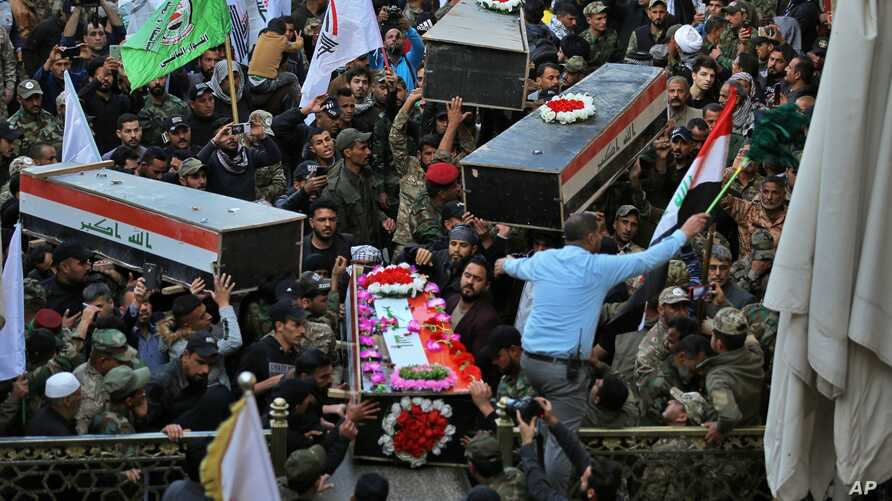 Mourners carry the coffins of Iran-backed Popular Mobilization fighters killed in a U.S. airstrike in Qaim, during their…
