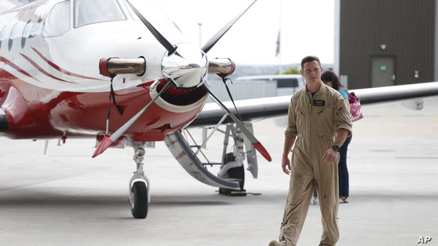 FILE - A pilot walks by a Pilatus PC-12 at Centennial Airport in the south Denver area, May 15, 2015. A Pilatus PC-12 crashed in South Dakota Saturday, killing nine of the 12 people on board. The NTSB is investigating.